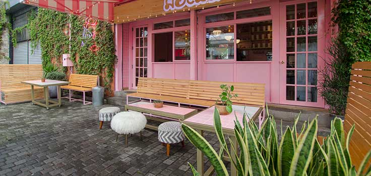 fachada de heladeria colo rosa con mesas afuera