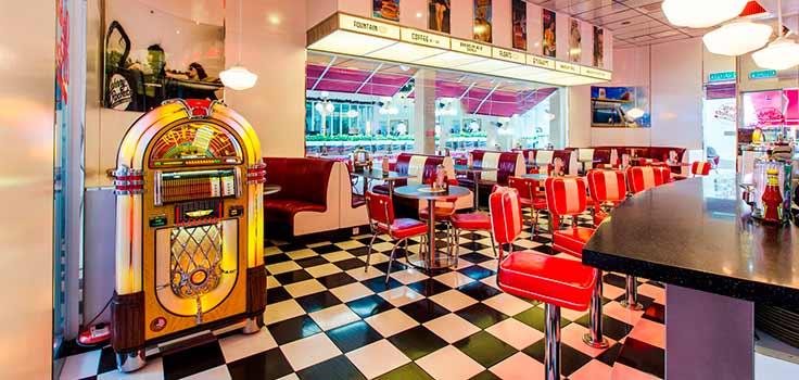 heladeria con piso blanco y negro cubiculos rojos y sillas rojas con rocola
