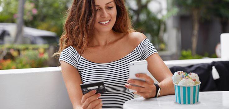 mujer sosteniendo su celular y tarjeta bancaria con un helado en la mesa