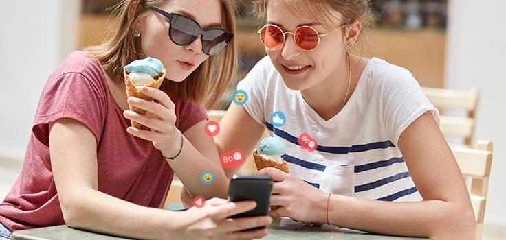 mujeres jovenes con helado en la mano y viendo un celular
