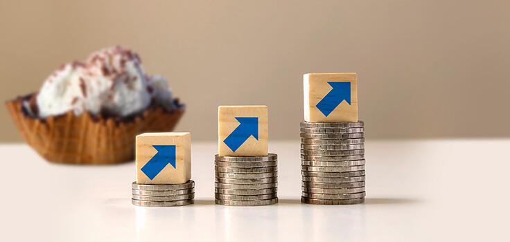 monedas y flechas en diagonal representando aumento de inversión en heladeria