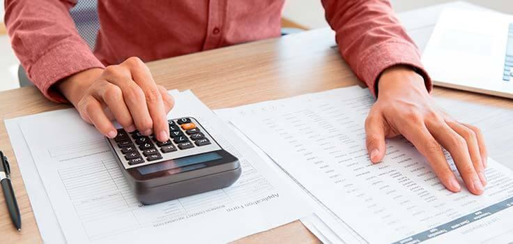 Persona realizando cuentas con calculadora en mano