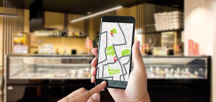 celular con mapa de ubicación frente a vitrina refrigerada