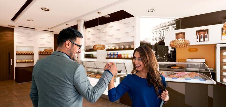 pareja estrechando las manos en el interior de heladería frente a vitrinas refrigeradas