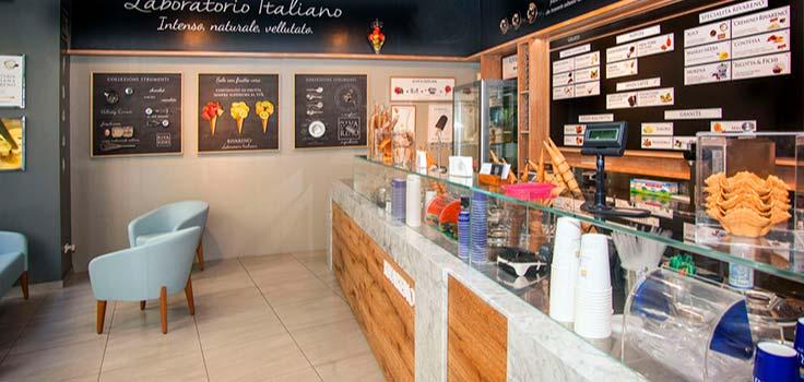 interior de heladeria con vitrina con vasos y conos de helado