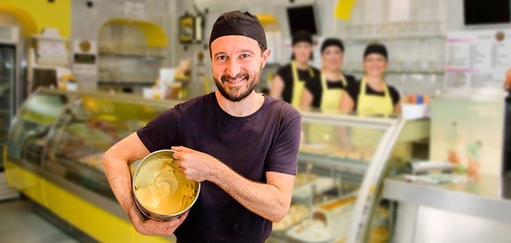hombre sosteniendo recipiente con helado frente vitrina refrigerada y personas