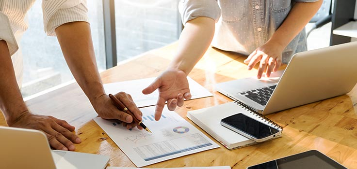 Personas revisando reportes con gráficas en una mesa junto a laptop, celular y otros artículos de oficina