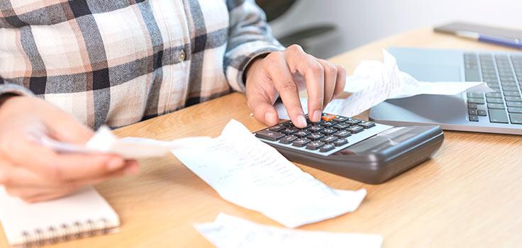 Persona realizando cuentas en una mesa con calculadora y recibo en mano