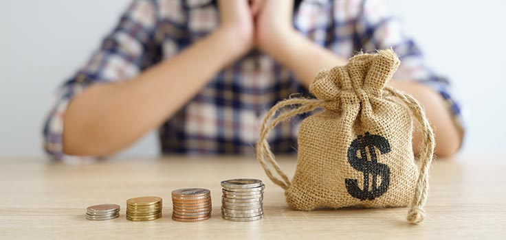 persona pensando en sus finanzas frente pila de monedas y saco con signo de precios en mesa