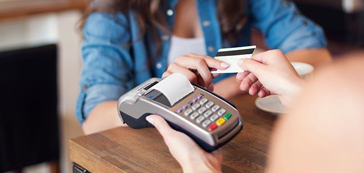 persona pagando con tarjeta de crédito frente a terminal bancaria