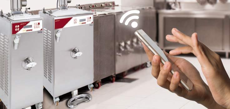 Persona sujetando celular en frente a dos máquinas pasteurizadoras para helados representando el manejo remoto